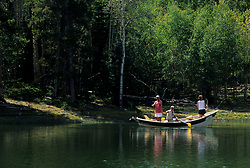 Stock photo of three people fishing from a boat on the lake