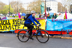 A cyclist passes the banners and tents as hundreds of environmental protesters from Extinction Rebellion occupy Marble Arch, camping in the square and even on the streets, blocking access to traffic on Park Lane and Oxford Street in London's usually traffic-heavy west end. . London, April 16 2019.