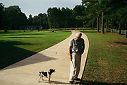 """MERIDIAN, MS – AUGUST 3, 2018: Clayton George, 57, surveys the family property alongisde his dog, Poupon. As a resident of Tennessee, George makes the four hour drive south every two weeks to check on his family's 400 acre tract and visit his father who still lives there.<br /> <br /> In 1987, George and a friend walked in rows planting the family's first batch of Loblolly pine, where soybeans, wheat and cattle once covered the family's 400 acres.  The shift to timber was largely prompted by the Conservation Reserve Program, a popular new farm subsidy in the 1980s that encouraged farmers to reforest depleted land by paying them for every acre of trees planted. Since 1926, the George family had made a good living from their eastern Mississippi farm, but the decline of soybeans and other crops eventually led George to consider growing trees instead –a crop that landowners throughout the south believed would bring in easy money. Thirty years later, however, the same landowners are now facing unexpected financial hardship. Stumpage prices have been on a steady decline – as much as 45% since 2007 – and landowners are rethinking timber as a worthwhile investment. """"""""We figured we''d plant trees and come back and harvest it in 30 years, and in the meantime go into town to make a living doing something else,"""" George said. As co-owner of the family acreage with three other family members, George always considered himself the most nostalgic Now, as he patiently awaits for right time to harvest a 30 year investment, even he considers the future of the land uncertain. CREDIT: Bob Miller for The Wall Street Journal<br /> TIMBER_AL"""