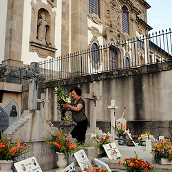 Pousada de Santa Marinha, Portugal -A woman places flowers on and cleans her father's grave at the cemetery adjacent to  the Pousada de Santa Marinha, a former convent nestled above the hills outside of Guimaraes, the first capitol of Portugal...Photo by Susana Raab