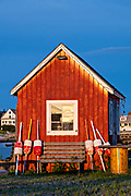 A red fish house against the blue sky during sunset at Orrs Island, Maine.