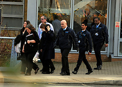 **CAPTION CORRECTION** © Licensed to London News Pictures. 30/01/2012, Staines, UK. Three protesters (far left) are escorted from a side entrance at British Gas headquarters in Staines, Surrey after being questioned by police. 6 activists barricaded themselves into meeting rooms on two floors of British Gas as part of the 'Winter Warm-Up' weekend called by the campaign group Fuel Poverty Action. British Gas is being targeted as one of the Big Six energy companies making profits out of rising energy bills.   Photo credit : Stephen Simpson/LNP