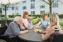 Multi-generation family playing board game at nursing home, Bavaria, Germany