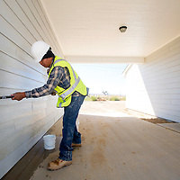 101513       Brian Leddy<br /> Davison Howe, a worker with Souers Construction, scrubs the siding of a home in a Navajo Housing Authority subdivision in Crownpoint Tuesday. The homes were recently remodeled at no cost to the owner, receiving a complete renovation.