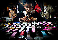 A man prepares wristwatches for sale at the night market in Hanoi, Vietnam