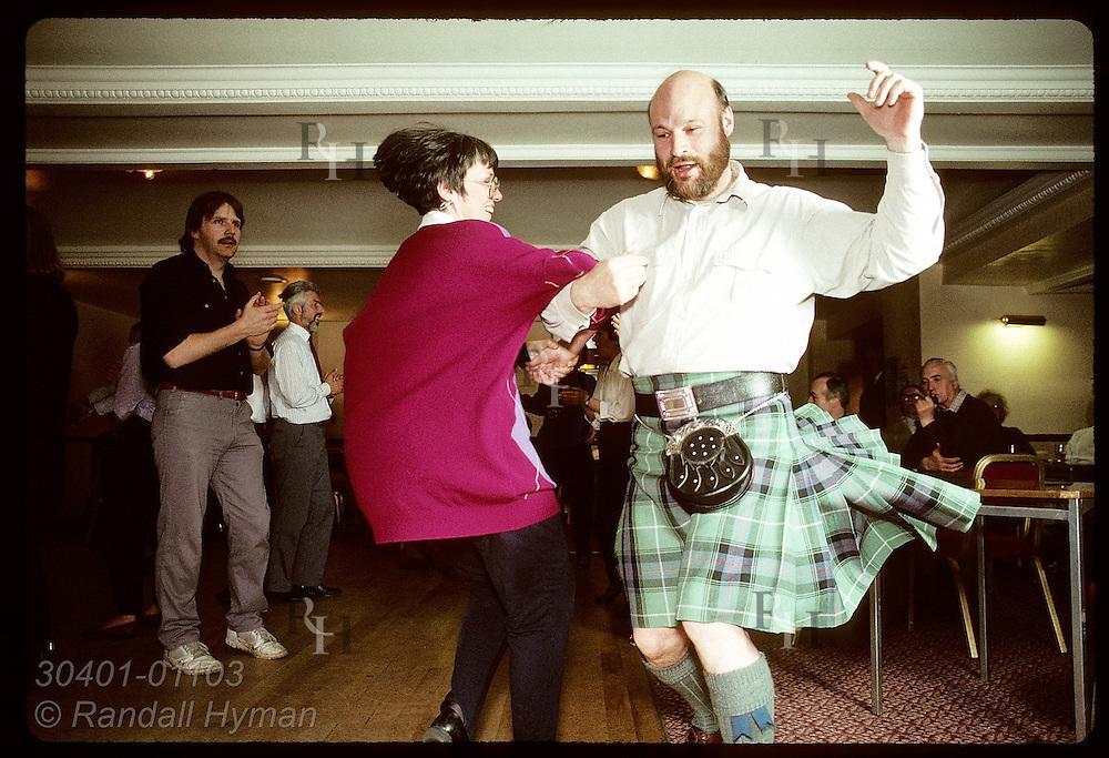Jim and Liz Houston swing around, arm in arm, at ceilidh dance @ the Black Bull Hotel; Milngavie. Scotland