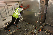 Using the Ball Mat Flooring System, below economy class flooring, a cargo handler manhandles a container of freight in the hold of a Sri Lankan Airlines Airbus A340