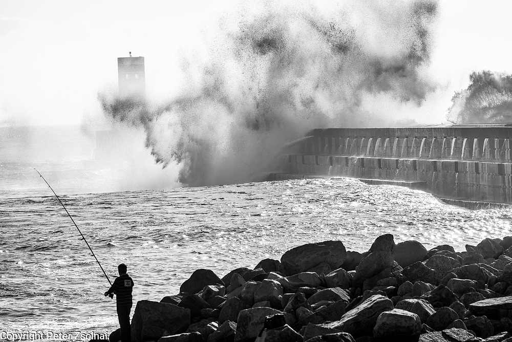 Huge waves crashing against the piers in Porto, Portugal, while a person is fishing in the save waters of the Atlantic Ocean.