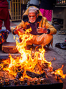 07 MARCH 2017 - KATHMANDU, NEPAL: A man warms himself at a fire at the Kamaladi Ganesh Temple, the most important Hindu temple dedicated to Ganesh, known as the overcomer of obstacles, in Kathmandu. In Hindu theology, Tuesdays are the best day to pray to Ganesh and the temple is very busy on Tuesdays. People frequently visit temples dedicated to Ganesh when they buy a new home or start a new job.     PHOTO BY JACK KURTZ