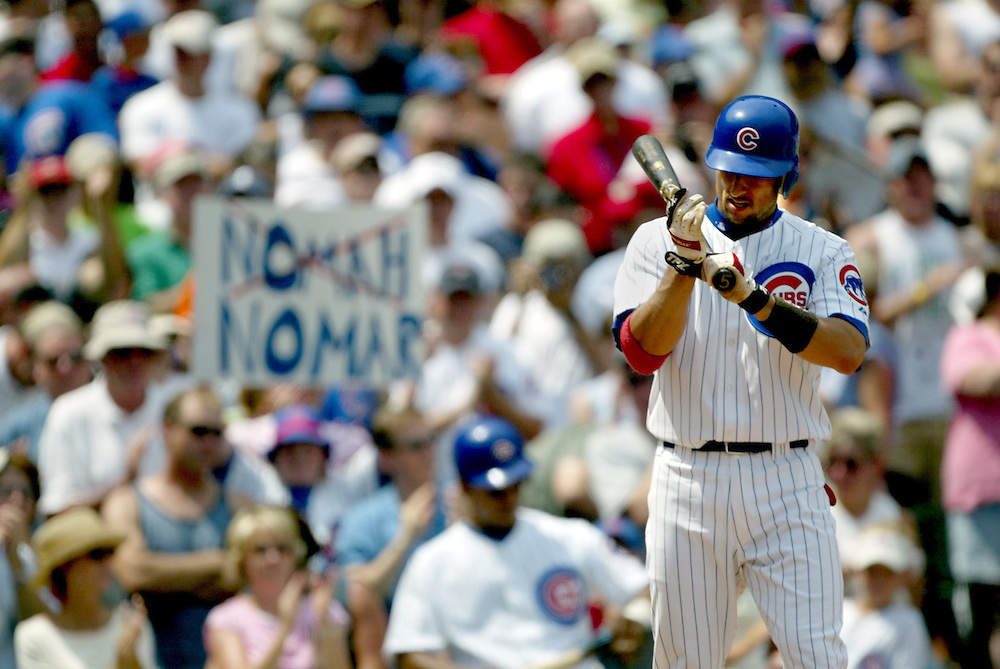 8/1/04 -- CHICAGO -- Cubs shortstop Nomar Garciaparra adjusts his gloves in his first at bat in a Cubs uniform while the Chicago fans remind him that he isn't in Boston anymore on Aug. 1, 2004.