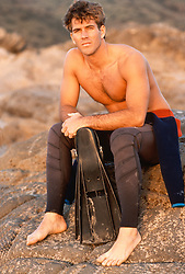Good looking man holding flippers sitting on a rock in California