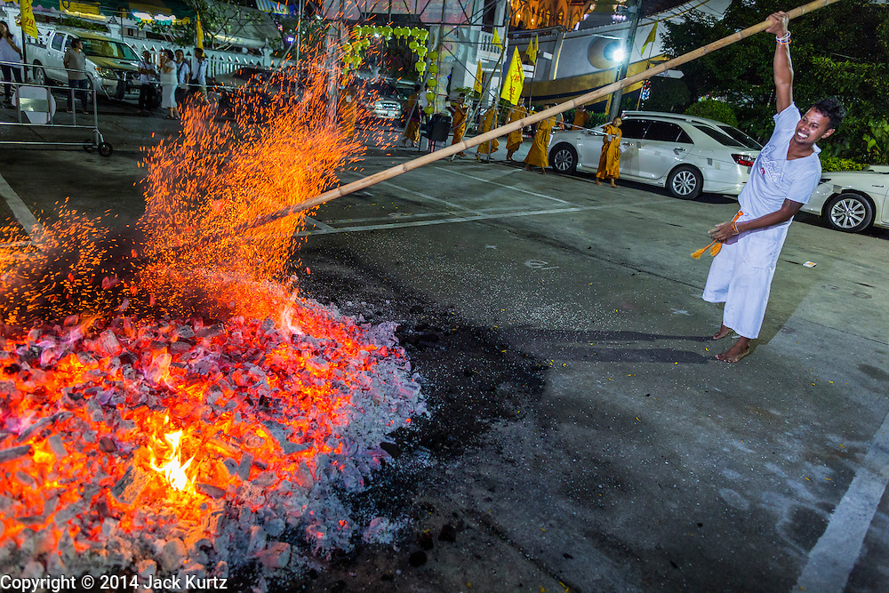 01 OCTOBER 2014 - BANGKOK, THAILAND: A fire tender stokes the fire pit before the firewalking at Wat Yannawa (also spelled Yan Nawa) during the Vegetarian Festival in Bangkok. The Vegetarian Festival is celebrated throughout Thailand. It is the Thai version of the The Nine Emperor Gods Festival, a nine-day Taoist celebration beginning on the eve of 9th lunar month of the Chinese calendar. During a period of nine days, those who are participating in the festival dress all in white and abstain from eating meat, poultry, seafood, and dairy products. Vendors and proprietors of restaurants indicate that vegetarian food is for sale by putting a yellow flag out with Thai characters for meatless written on it in red.     PHOTO BY JACK KURTZ