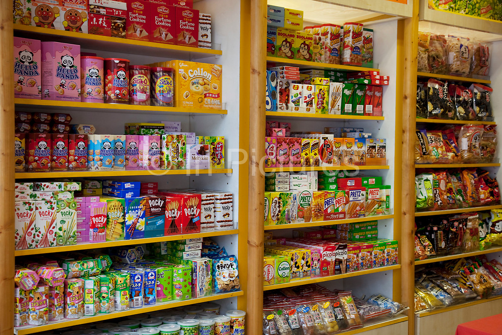 Scene in London's famous Chinatown around Gerrard Street. Colourful Chinese snacks in garish packaging in a snack shop