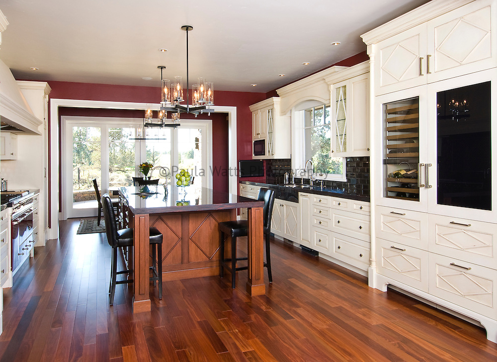 Traditional kitchen with white cabinetry and red accents and custom sub zero refrigerator