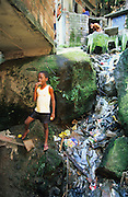 CHILDREN NEAR OPEN SEWERS. Rocinha Favela, Rio de Janeiro, Brazil, South America. Children sitting near open sewers. Although Rocinha is technically classified as a neighborhood, many still refer to it as a favela. It developed from a shanty town into an urbanized slum. Today, almost all the houses in Rocinha are made from concrete and brick. Some buildings are three and four stories tall and almost all houses have basic sanitation, plumbing, and electricity. Compared to simple shanty towns or slums, Rocinha has a better developed infrastructure and hundreds of businesses. There is also lots of deliquency, crime and drugs in the favelas.