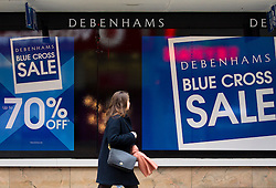 © Licensed to London News Pictures. 08/01/2013. London, UK.  A shoppers walks past signs for the Debenham's 'Blue Cross Sale' displayed in the chain's flagship Oxford Street store in London today (08/01/13).  The department store chain today reported record December sales, achieved in part by additional promotions, with like-for-like sales rising by 2.9% compared to the same period in 2011/12 and online sales boosted by 39%.  Photo credit: Matt Cetti-Roberts/LNP