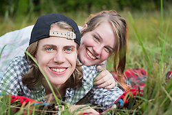 Portrait of a young couple lying in meadow and smiling, Bavaria, Germany