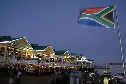 South African flag at dusk beside shopping and cafe area of the Victoria and Albert (V&A) waterfront, Cape Town, South Africa. (Credit Image: © Axiom/ZUMApress.com)