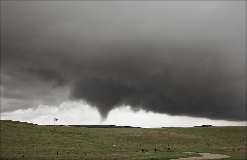 A tornado went through a farm field next to a windmill in Lincoln County Kansas.