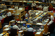 An interior of office desks and 90s computers in the trading floor of Barclays de Zoete Wedd in the City of London, the capital's financial centre. Screens glow with the most up to date trading figures and news items allowing traders to react instantly on the money markets.  <br /> Employees talk on handsets or stare at their data near large keyboards and hard drives and deep monitors were state of the art technology in the early 1990s.