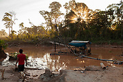 A miner walks alongside a flooded area used to extract gold by means of a truck engine machine, tubes and hoses in the Peruvian Amazon.