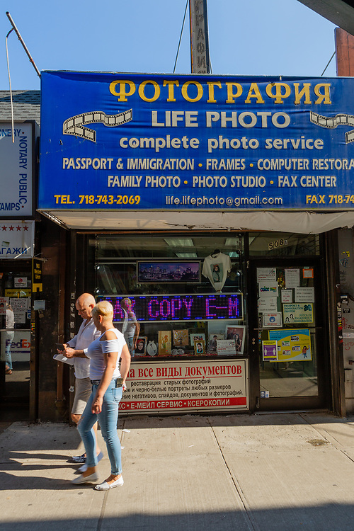 Life Photo, offering passport and immigration photos and fax and other services to the Russian-speaking community on Brooklyn's Brighton Beach Avenue. Much of the signage is in Russian, reflecting the dense population of Russian-speaking people in the area.