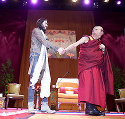 © Licensed to London News Pictures. 16/06/2012. Manchester , UK . The Dalai Lama leads Russell Brand off the stage at the end of the event . Russell Brand and The Dalai Lama at the Manchester Arena , Greater Manchester , at the Stand Up and Be the Change youth event . The Dalai Lama is on a 10 day tour of the UK . Photo credit : Joel Goodman/LNP