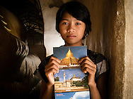 A girl sells postcards in a temple in Bagan, Myanmar, Southeast Asia, December 2012.
