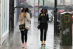© Licensed to London News Pictures. 17/05/2021. London, UK. Women shelter from heavy rain beneath umbrellas in north London. More rain is forecast for the South East of England this week. Photo credit: Dinendra Haria/LNP