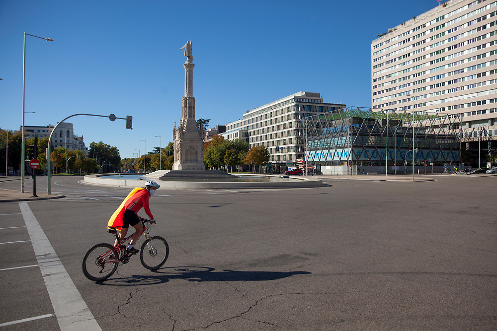 MADRID, SPAIN - OCTOBER 12: A cyclist wearing face mask and a Spanish flag rides by an empty Plaza de Colón (Columbus Square) with Columbus statue in the background, on October 12, 2020 in Madrid, Spain. This year the traditional Spanish National Day military parade alongside the Paseo de la Castellana in Madrid has been canceled due to the Covid-19 pandemic and replaced by a more discreet event at the Royal Palace. (Photo by Miguel Pereira/Getty Images)