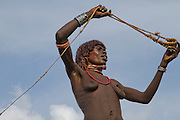 Africa, Ethiopia, Omo River Valley Hamer Tribe woman hunts with a slingshot