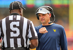 Sep 14, 2019; Morgantown, WV, USA; West Virginia Mountaineers head coach Neal Brown talks to an official during the second quarter against the North Carolina State Wolfpack at Mountaineer Field at Milan Puskar Stadium. Mandatory Credit: Ben Queen-USA TODAY Sports