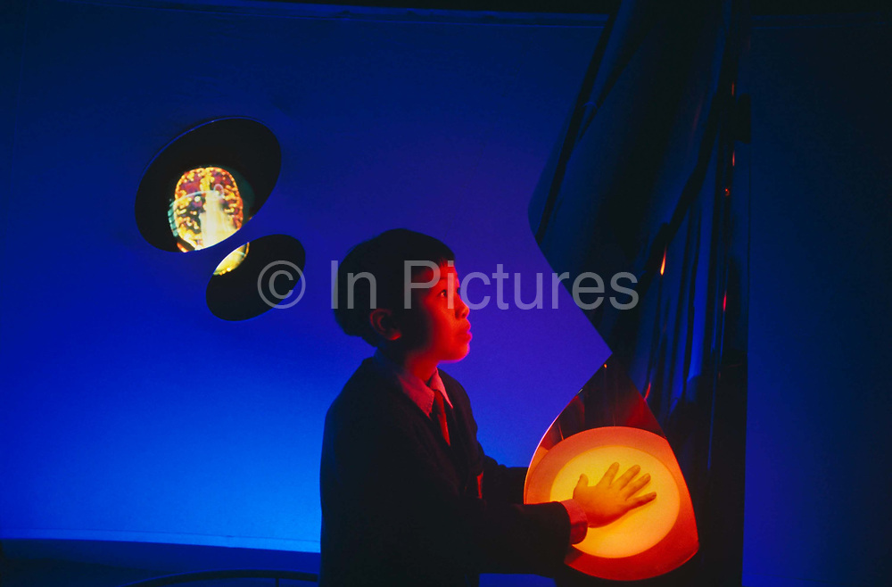 A young Chinese boy on a school trip places his hand on an exhibit belonging to the British communications company, Cable & Wireless at the Hong Kong Telecom Tower in Central Hong Kong. The smartly-dressed lad dressed in his school uniform is seen against a graduated blue background and is placing his hand on a sensor to activate an interactive demonstration. His face glows with the red light from the programme and his hands is being read by the orange light of the sensor. Since 1938 Cable & Wireless became responsible for the fixed wireless services of Hong Kong and connected their external telephone services for the national network. The services operate on one of the most highly advanced fibre optic networks in the world. Cable & Wireless provides  domestic and international telecommunications services in Hong Kong through the operating companies of its subsidiary, Hong Kong Telecom.