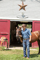 cowboy enjoying time with his horse by a barn