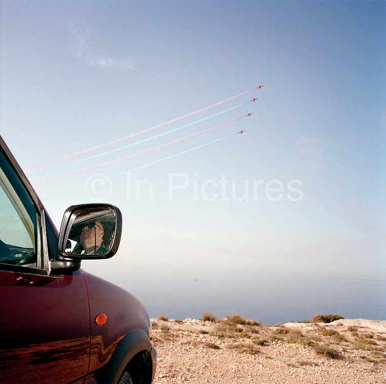 Hawk jets of the Red Arrows, Britain's RAF aerobatic team practice display over a pilot officer who sits in his cool car on the cliff edge at RAF Akrotiri, a British-run RAF air base in southern Cyprus, using this coastal cliff as display datum (centre). Looking out to the Mediterranean Sea from the Akrotiri Peninsular, Cyprus, we see the elite team, practising their display, a show-stopping manoeuvre of their 25-minute air show display routine. 'Datum' is an axis on which the Red Arrows focus their displays, from where the whole show is visible at the crowd's centre. The cliffs are but one of a series of datum points selected by the team leader at short notice to simulate diverse geographical features and wind directions