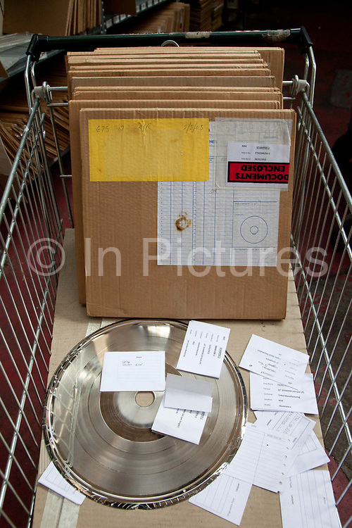 Records in cardboard ready to ship, with a siler test disk, all sitting in a shopping trolley. The Vinyl Factory is the old EMI vinyl works in Uxbridge, Middlesex, producing limited edition vinyls of new releases, plus re-presses of classics. They also act as a distributor of vinyl releases.