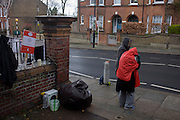 Wendy, in red, a lifelong campaigner and activist stands outside Carnegie Library in Herne Hill, south London asking passing motorists to hoot their support, while occupiers remain inside the premises on day 7 of its occupation, 6th April 2016. The angry local community in the south London borough have occupied their important resource for learning and social hub for the weekend. After a long campaign by locals, Lambeth have gone ahead and closed the library's doors for the last time because they say, cuts to their budget mean millions must be saved.