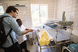 "2 March 2017, Morija, Maseru district, Lesotho: Adam Creighton, development director of InStove, talks to a nurse at Scott Hospital, inquiring about a sleeping child. The child, which sleeps next to the hospital's incubation machines, is called a ""lost and found"" by the nurses. The child was found 7 days ago, crying alone in a field near the hospital. The hospital has taken the child in for care, the police are trying the locate the child's family, and a social worker has been assigned to the case. The child is a suspected orphan. ""It's rare to find orphans like this, but it's not the first time"" say the nurses at Scott's. Scott Hospital is run by the Lesotho Evangelical Church in Southern Africa and is a founding member of the Christian Health Association of Lesotho. It is located in the village of Morija, and operates and supervises clinics in the Maseru District of Lesotho. Scott started out as a dispensary in 1864, and today offers comprehensive healthcare Mondays-Fridays, as well as pharmaceutical services around the clock. Lesotho suffers from high numbers in Tuberculosis in disesase and mortality, and so the hospital screens all patients for TB. The hospital observes among many patients what they describe as ""low health-seeking behaviour"", services are increasing and demand rising, but space and human resources are a challenge, as is funding. I key concern is one of infrastructure, where the original design of the hospital matches poorly with current needs, as departments and buildings are scattered, posing a challenge for security. Another challenge is to adapt donation structures, so as to be able to receive payments electronically. The hospital has one ambulance, which they describe as not enough, but what they have. Another challenge is that lack of funds affects maintenance of buildings and infrastructure, as the immediate care of patients take priority. PLEASE NOTE: This photo is not to be used in social media."
