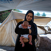 Hanan, 33, from Idlib, Syria, holding her son, Ahmed, 25 days, the youngest refugee in the camp. Ritsona Refugee Camp, Greece, July 2016.