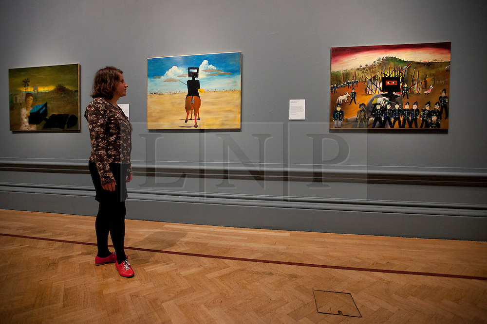 © Licensed to London News Pictures. 17/09/2013. London, UK. A member of gallery staff looks at 'Ned Kelly' (1946) (left), Glenrowan (1970-1) (R) and 'Quilting the Armour' (1971) (L), painted by Australian artist Sidney Nolan as part of his iconic series about the Australian outlaw, at the press view for the Royal Academy of Arts latest exhibition 'Australia' in London today (17/09/2013). The exhibition, said to be the most significant survey of Australian art ever mounted in the UK, spans more than 200 years, from 1800 to the present, and runs from the 21st of September to the 8th of December 2013. Photo credit: Matt Cetti-Roberts/LNP