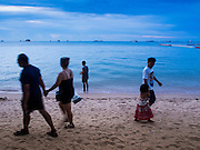 """26 SEPTEMBER 2014 - PATTAYA, CHONBURI, THAILAND: Tourists walk along Pataya Beach. Pataya, a beach resort about two hours from Bangkok, has wrestled with a reputation of having a high crime rate and being a haven for sex tourism. After the coup in May, the military government cracked down on other Thai beach resorts, notably Phuket and Hua Hin, putting military officers in charge of law enforcement and cleaning up unlicensed businesses that encroached on beaches. Pattaya city officials have launched their own crackdown and clean up in order to prevent a military crackdown. City officials have vowed to remake Pattaya as a """"family friendly"""" destination. City police and tourist police now patrol """"Walking Street,"""" Pattaya's notorious red light district, and officials are cracking down on unlicensed businesses on the beach.     PHOTO BY JACK KURTZ"""