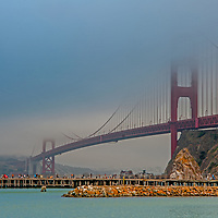 Tourist watch fog envelop the Golden Gate Bridge that spans between San Francisco and Marin County in California.  (Viewed from near Cavallo Point in Sausalito.)