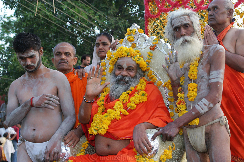 A Sadhu (Hindu ascetics) with his naga followers on a float during a parade during the Kumbh Mela festival, Ujjain, Madhya Pradesh, India. The Kumbh Mela festival is a sacred Hindu pilgrimage held 4 times every 12 years, cycling between the cities of Allahabad, Nasik, Ujjain and Hardiwar.  Participants of the Mela gather to cleanse themselves spiritually by bathing in the waters of India's sacred rivers. Kumbh Mela is one of the largest religious festivals on earth, attracting millions from all over India and the world. Past Melas have attracted up to 70 million visitors.