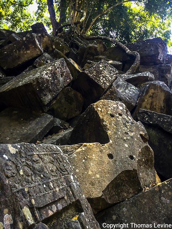 Stone block in a pile with holes in the block at Beng Melia, Angkor Temple