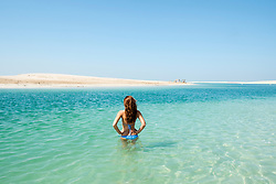 Woman in sea at The Island Lebanon beach resort on a man made island, part of The World off Dubai coast in  United Arab Emirates
