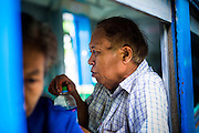 15 JUNE 2013 - YANGON, MYANMAR: A passenger drinks a bottle of water on the Yangon Circular Train. The Yangon Circular Railway is the local commuter rail network that serves the Yangon metropolitan area. Operated by Myanmar Railways, the 45.9-kilometre (28.5mi) 39-station loop system connects satellite towns and suburban areas to the city. The railway has about 200 coaches, runs 20 times and sells 100,000 to 150,000 tickets daily. The loop, which takes about three hours to complete, is a popular for tourists to see a cross section of life in Yangon. The trains from 3:45 am to 10:15 pm daily. The cost of a ticket for a distance of 15 miles is ten kyats (~nine US cents), and that for over 15 miles is twenty kyats (~18 US cents). Foreigners pay 1 USD (Kyat not accepted), regardless of the length of the journey.     PHOTO BY JACK KURTZ