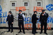 Police officers stand in front of a wall covered in graffiti  by the entrance of Shell oil HQ on 15th April 2019 in London, United Kingdom.  Extinction Rebellion a climate change protest group are protesting  across the centre of London and plan to block traffic for the next five days.