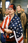 "11 JANUARY 2021 - DES MOINES, IOWA: A woman draped in an American flag applauds a speaker who talked about personal freedom in the Rotunda of the Iowa State Capitol in Des Moines. Hundreds of Iowans, from across the state, came to the State Capitol to protest the Governor's COVID-19 mitigation efforts. The Coronavirus (SARS-CoV-2) mitigation guidelines include a mask mandate indoors when it isn't possible to social distance. But the Governor specifically exempted the State Capitol. No one in the crowd wore a mask and there was no effort to follow ""social distancing"" guidelines. There were also ""anti-Vaxxers"" in the crowd who protested the vaccine efforts and said vaccines were unsafe.           PHOTO BY JACK KURTZ"