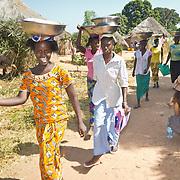 Koumbadiouma womenfolk pass Peace Corps volunteer Rachael Honick and her faithful dog, Yoda. Kolda, Senegal.