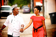 Bride in her red engagement dress holding hands with the groom and walking through Deep Ellum.